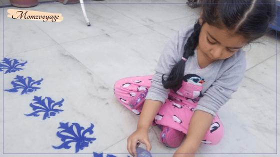 little girl busy in making rangoli